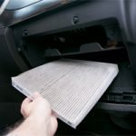 person replacing an in-cabin air filter