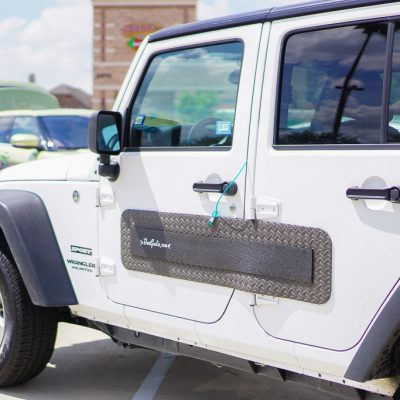 DentGoalie car door protection panels on a white jeep in a parking lot.